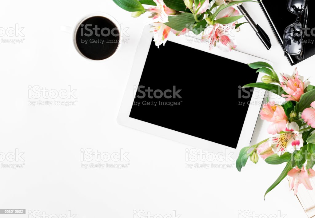 office desk with tablet with blank screen, office accessories, cup of coffee and bouquet of flowers stock photo