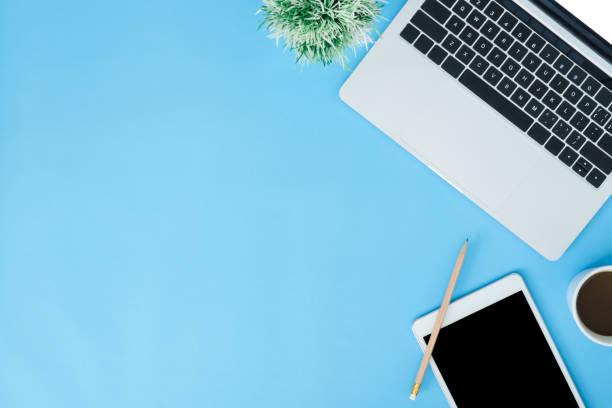 Büro-Schreibtisch Arbeitsraum-Flach-Lay-op-Top-Mockup-Foto von Arbeitsraum mit Laptop, intelligentes Gerät und eine Tasse Kaffee auf blauem Pastell-Hintergrund. Pastellblauer Farbkopierraum Arbeitsraumkonzept. – Foto