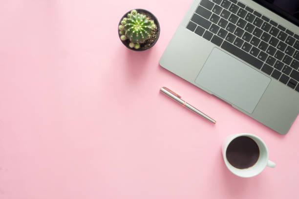 Büroschreibtisch Arbeitsraum - Wohnung lag Draufsicht des modernen Arbeitsbereich mit warmen Kaffee Tasse, Laptop, Stift und Pflanze textfreiraum auf Pastell farbigen Hintergrund. Rosa Farbe Hintergrund Schreibtisch Arbeitskonzept. – Foto