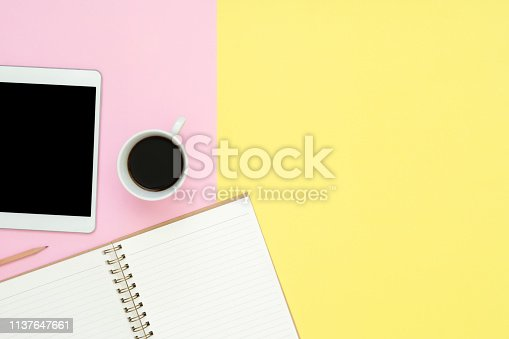 Office desk working space - Flat lay top view photo of working space with blank mock up tablet, coffee cup and notebook on pastel background. Pastel pink yellow color copy space working desk concept.