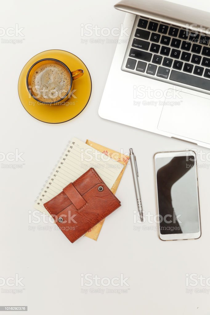Office desk workspace. Top view. Wallet, laptop, phone and a cup of...
