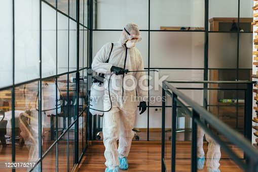 Man in protective suit and face mask spraying for disinfection in the office