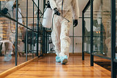 Man in protective suit using spray bottle with disinfectant for decontamination and cleaning in the office