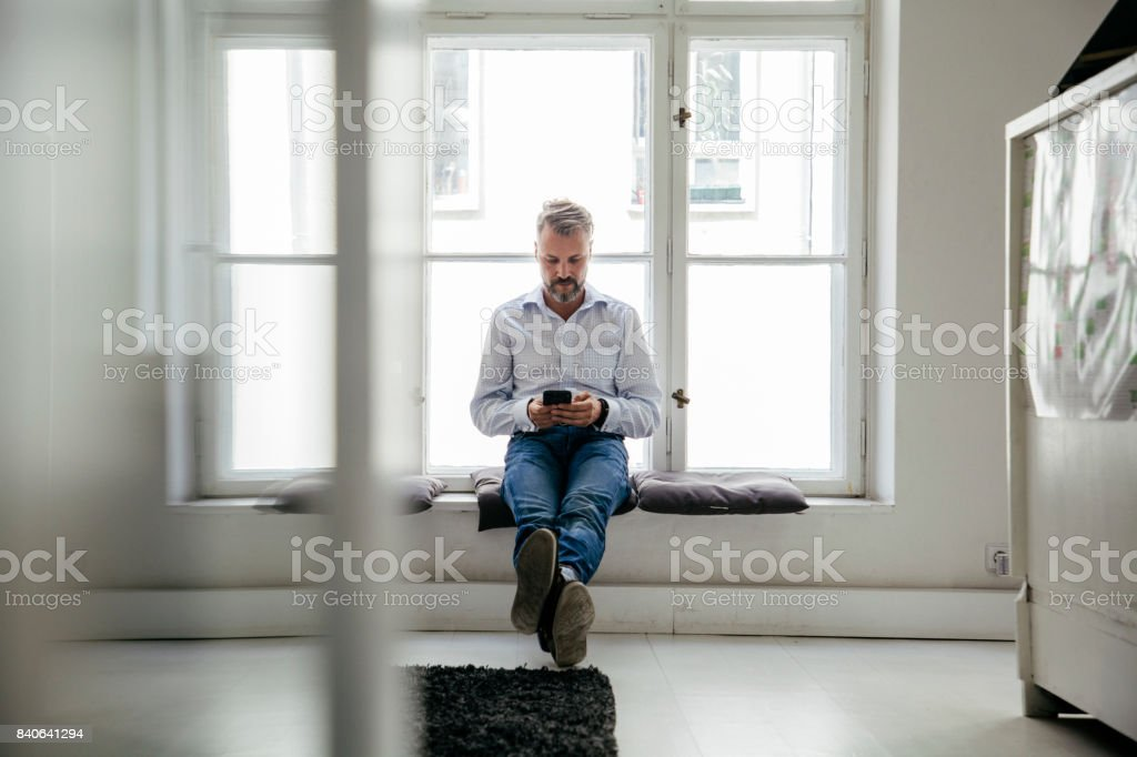 Office Employee Sat By Window Taking Break From Work An office employee taking a break from work to sit by the window and look at his smartphone. Adult Stock Photo