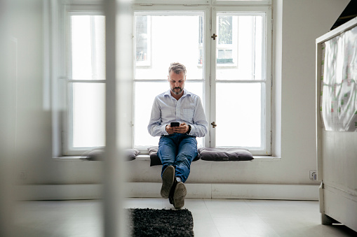 Office Employee Sat By Window Taking Break From Work Stock Photo - Download Image Now