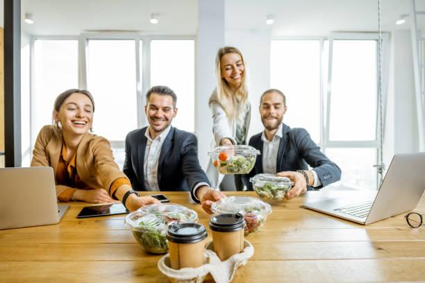 Kantoormedewerkers met gezond afhaalmaaltijden binnenshuis foto
