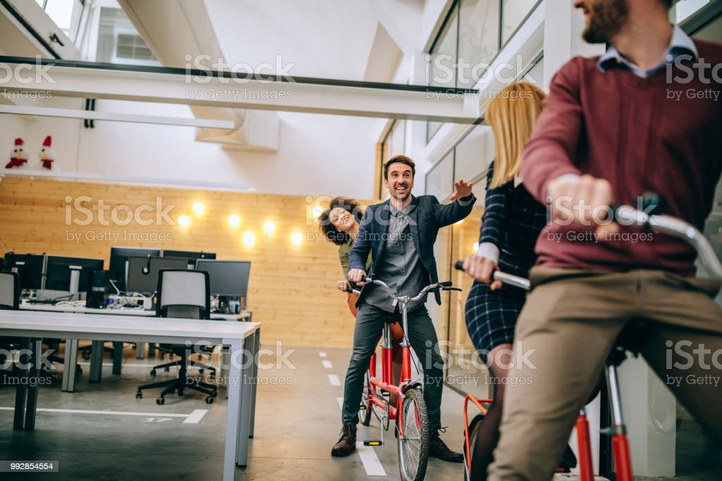 Shot of four coworkers riding tandem bicycles at their workplace