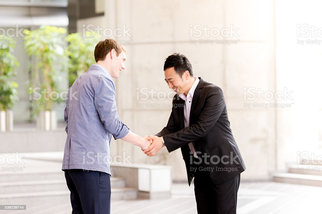 Office Executives handshaking and bowing with respect. royalty-free stock photo