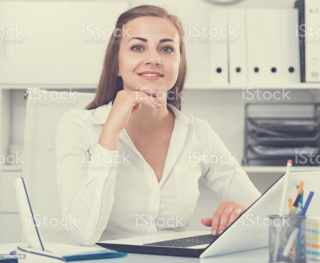 Weibliche Büroangestellte posiert während der Arbeit hinter laptop - Lizenzfrei Aktivitäten und Sport Stock-Foto