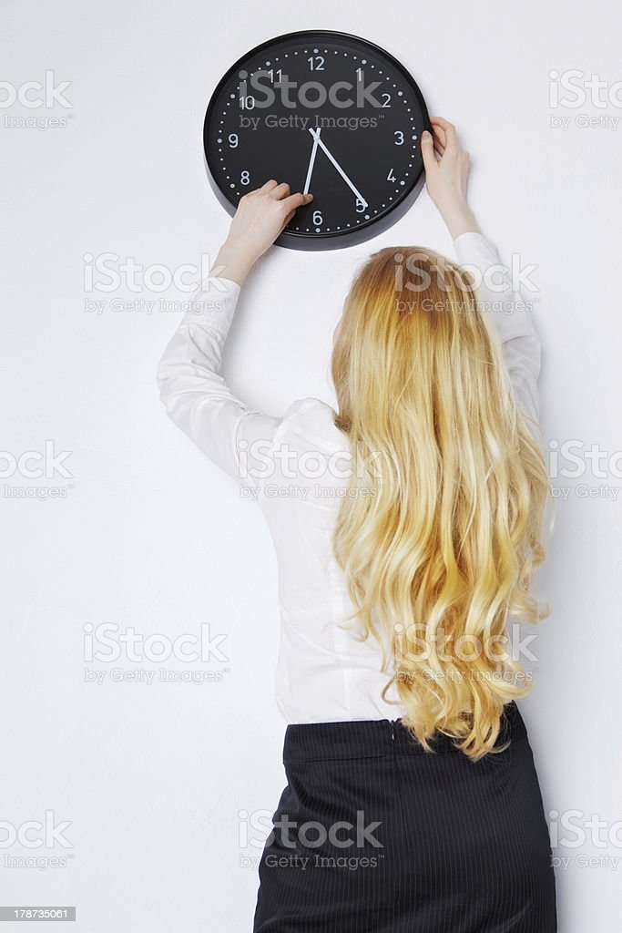 Office Girl Sets the Clock stock photo
