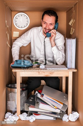 businessman working in an office in a box - concept small office