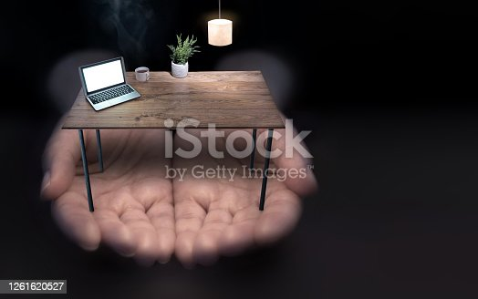 Hands holding miniature office with laptop and lamp