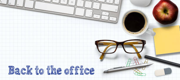 office items and the message BACK TO THE OFFICE on paper background stock photo