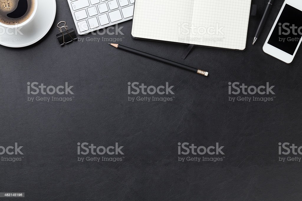 Office leather desk with computer, supplies and coffee stock photo
