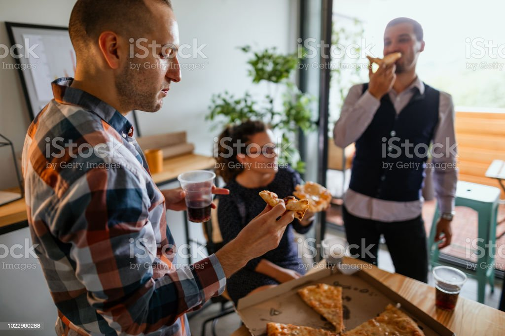 Photo of business team eating pizza in the office
