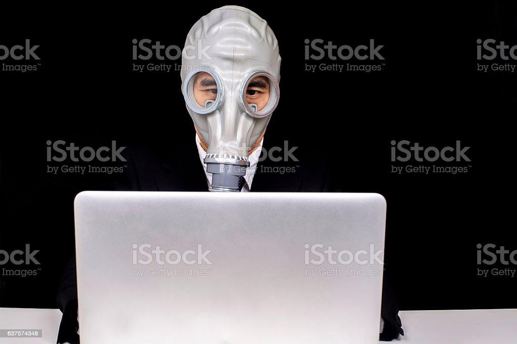 office man wearing gas mask, working on laptop stock photo