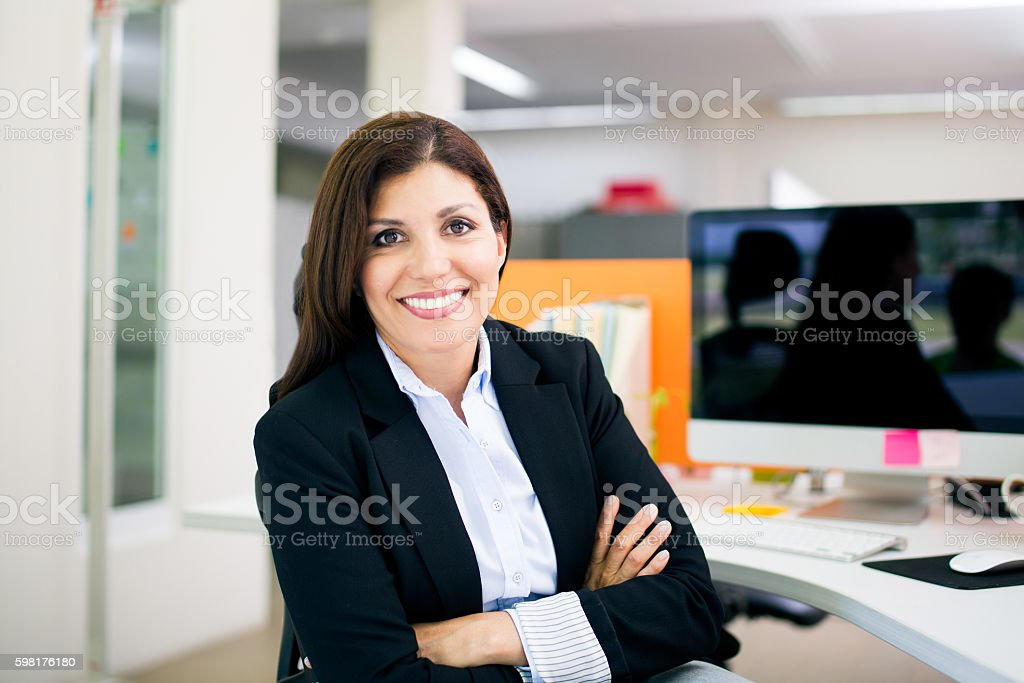 Office manager smiling at camera with arms crossed stock photo