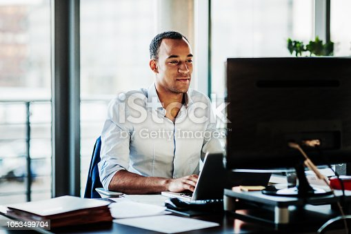 An office worker using working at his desk using a computer to review data.