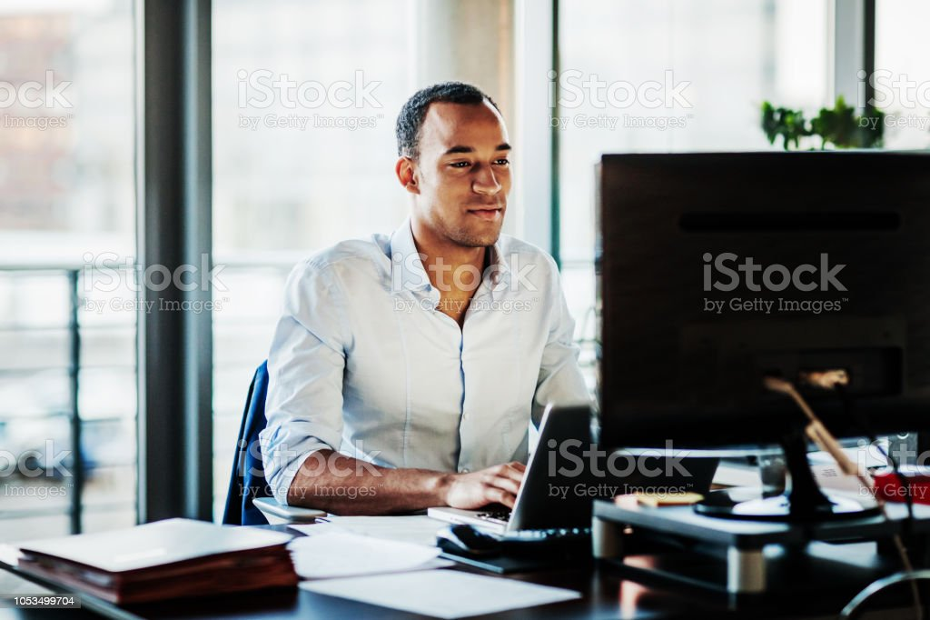 Office Manager Working On Computer At His Desk stock photo