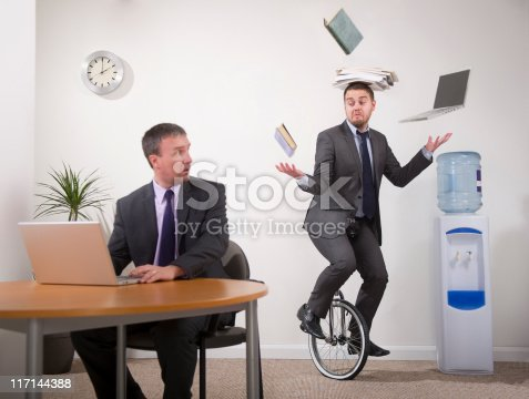 younger office worker shows older colleague how to multi-task