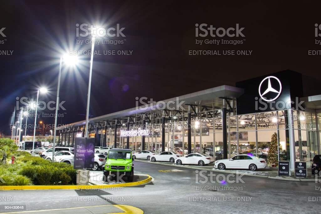 Vancouver BC, Canada - January 9, 2018: Office of official dealer Mercedes-Benz. Mercedes-Benz is a German automobile manufacturer Night shot all sings and inside of the building is illuminated. stock photo