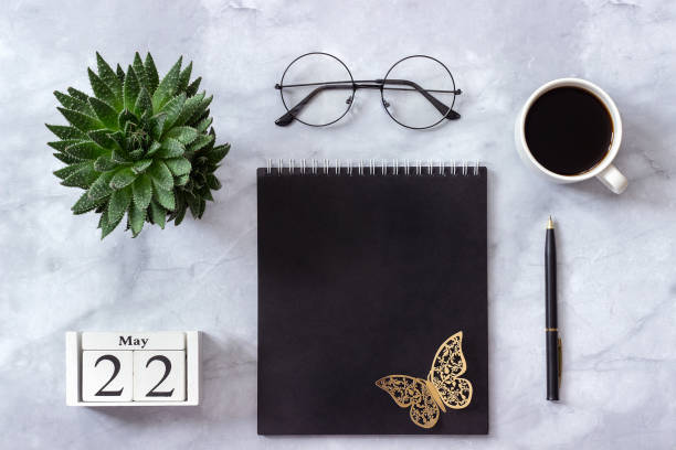 Office or home table desk. Wooden cubes calendar May 22. Black notepad, cup of coffee, succulent, glasses on marble background Concept stylish workplace Flat lay Top view stock photo
