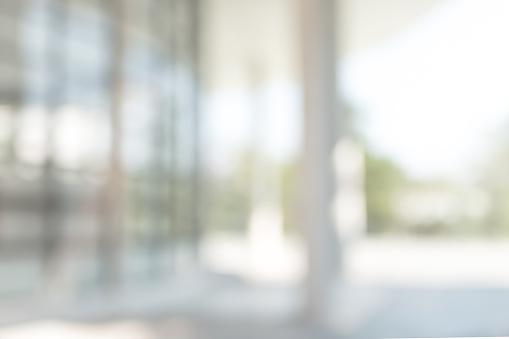 Office or university building blur background exterior view with blurry empty lobby space, entrance hall glass wall window and light bokeh