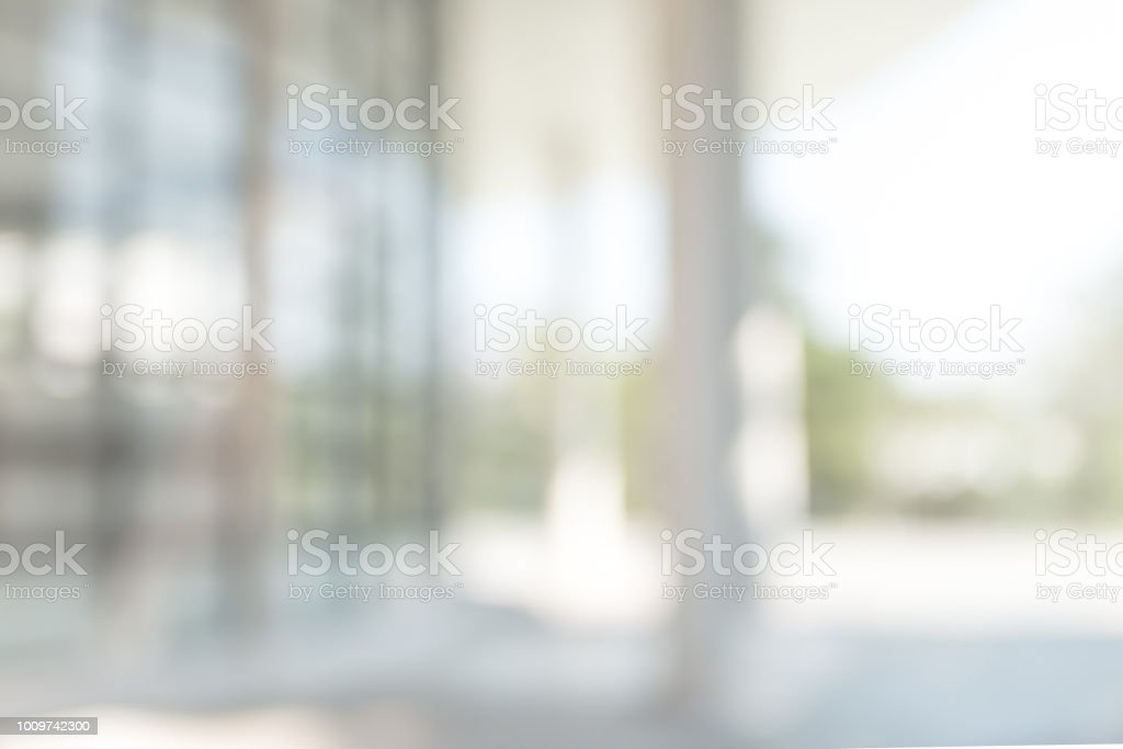 Office or university building blur background exterior view with blurry empty lobby space, entrance hall glass wall window and light bokeh stock photo