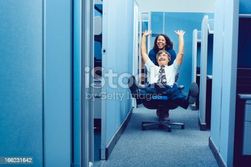 Co-workers racing through cubicles with office chair.