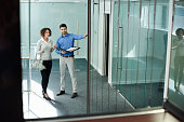 a young business woman is being shown around some empty office space by a real estate agent .