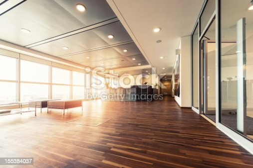 A large open plan office space with a wooden floor and decorative ceiling.  Full height windows run along the full length of the office space.