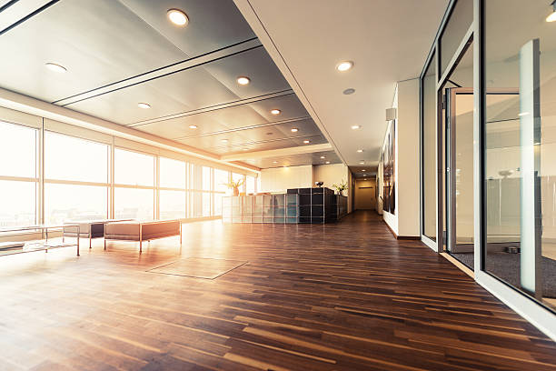 Office reception with wood floors and window wall A large open plan office space with a wooden floor and decorative ceiling.  Full height windows run along the full length of the office space. ceiling stock pictures, royalty-free photos & images