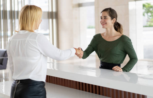 Office receptionist greeting corporate partner Office receptionist greeting corporate partner with handshake. Woman in formal clothing shaking hands over reception counter. Partnership concept checkout stock pictures, royalty-free photos & images