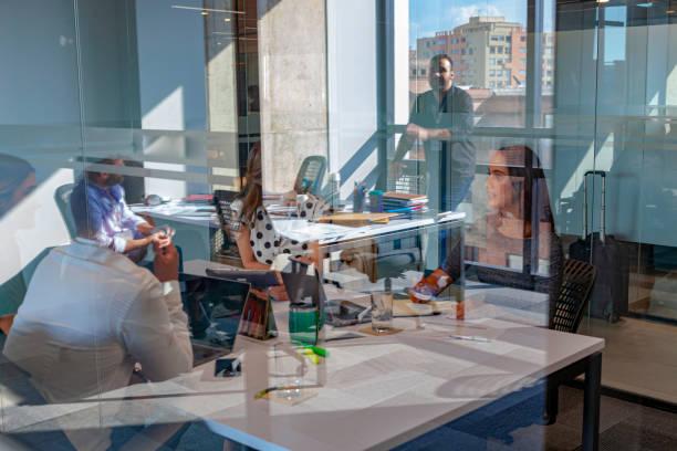 Office Reflections - Lateinamerikanische Millennial Generation Angestellte angestellte Arbeiter bei einem Geschäftstreffen in einem Büro mit Laptops und andere Technologie; Reflexionen eines anderen Office in Bild aufgenommen, Mischen Sie alles sichtbar. – Foto