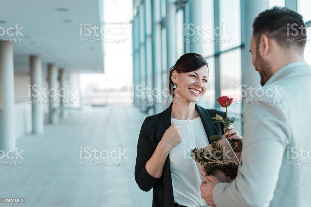 Büro-Romantik. Mann seine weiblichen Kollegen eine Rose geben. Frauentag – Foto