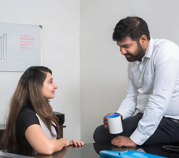 Office Romance Two young office executives are flirting at their workstation. romance stock pictures, royalty-free photos & images