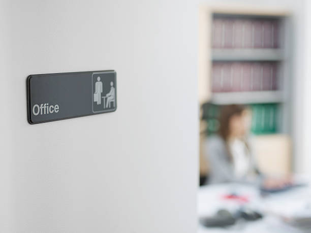 Office Sign with Worker in Background stock photo
