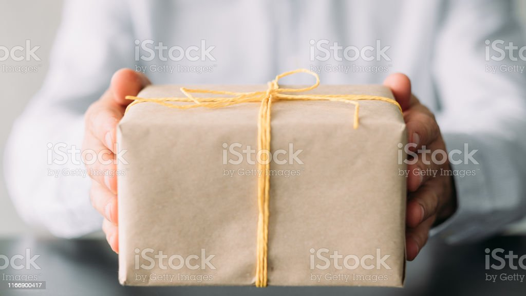 Office snacks delivery service. Closeup of beige paper wrapped gift...