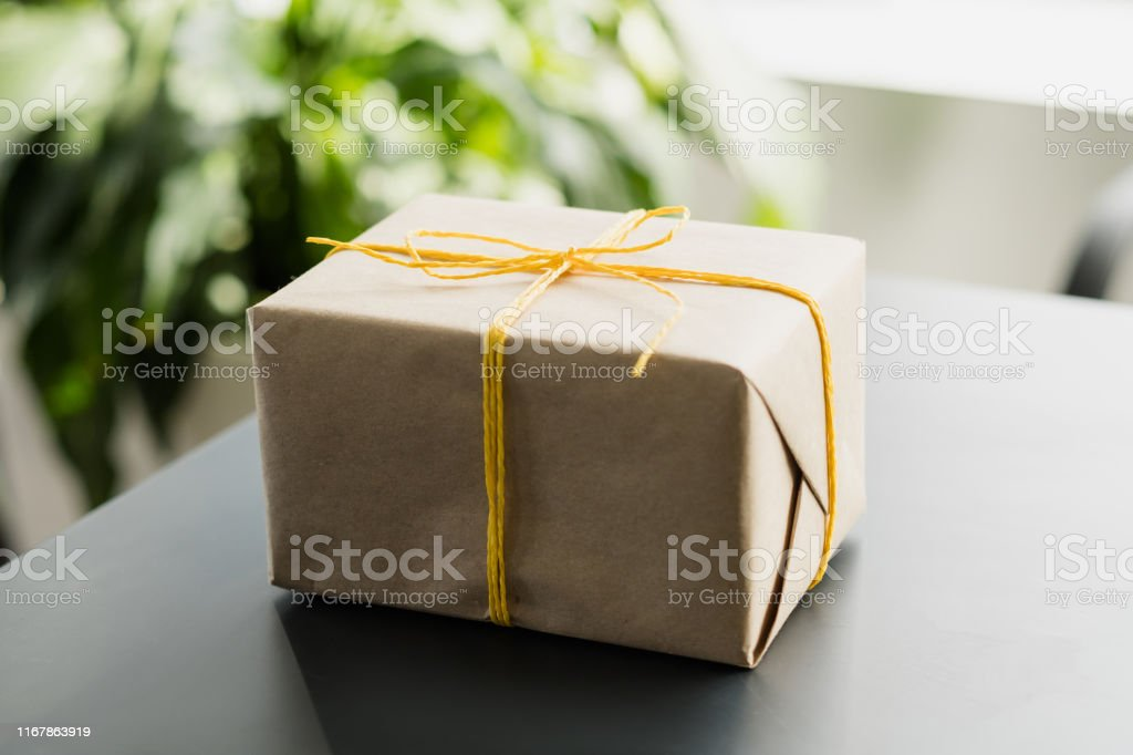 Office snacks delivery service. Closeup of beige paper gift box tied...