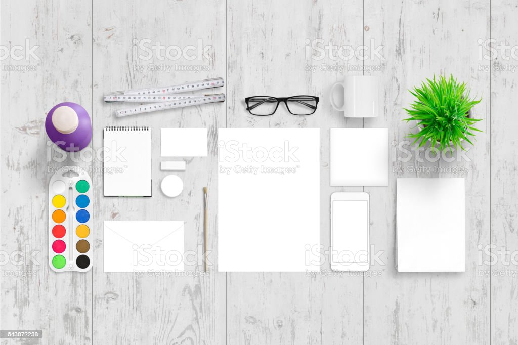 Office stationery for corporate branding. Top view of white wooden desk with paper, pad, bag, envelope, business card, badge, mug, plant, glasses, water colors, brush and smart phone. stock photo