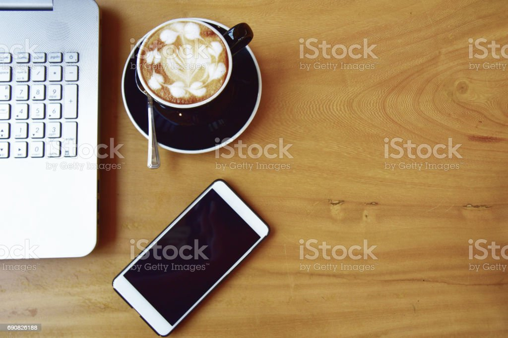 office stuff with smart phone laptop and coffee cup mouse notepad top view shot. stock photo