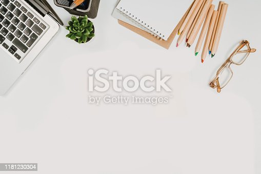 1173922060 istock photo office stuff with with notepad, laptop and coffee, glasses, notepad top view 1181230304