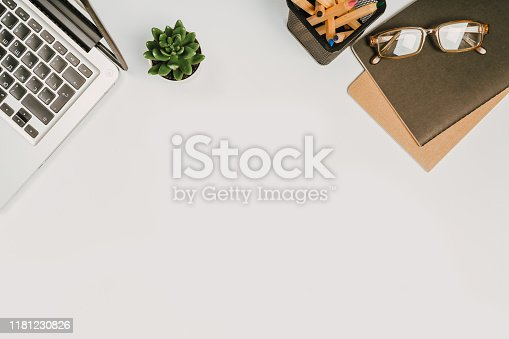 1173922060 istock photo office stuff with with notepad, laptop and coffee, glasses, notepad top view 1181230826