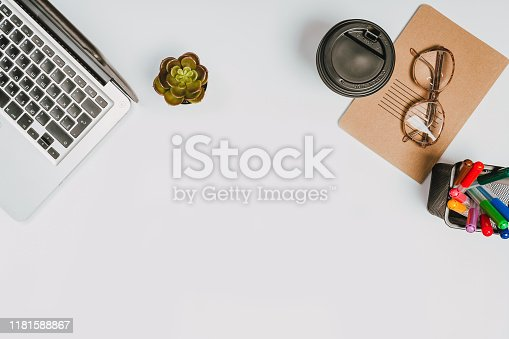1173922060 istock photo office stuff with with notepad, laptop and coffee, glasses, notepad top view 1181588867