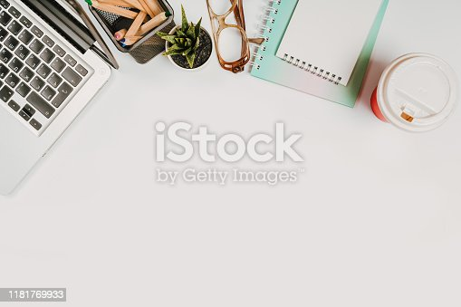 1173922060 istock photo office stuff with with notepad, laptop and coffee, glasses, notepad top view 1181769933