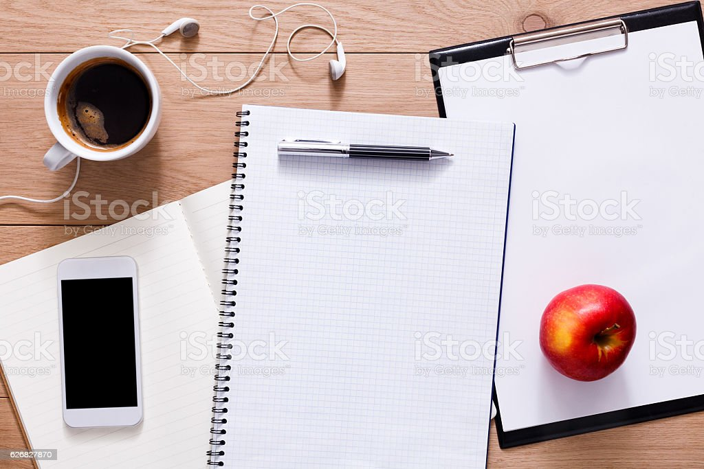 Office supplies and mobile phone at wood background stock photo