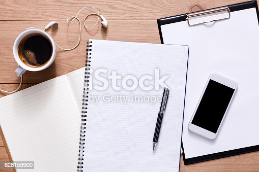 istock Office supplies and mobile phone at wood background 628159900