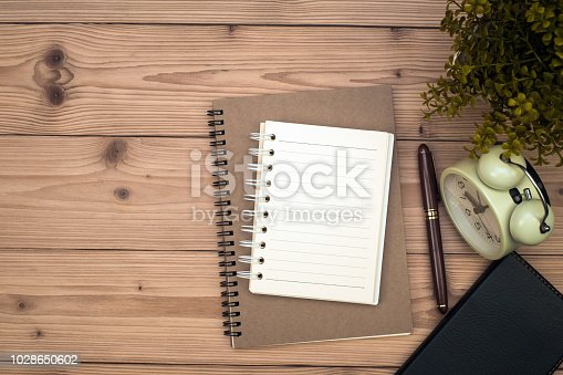 Office supplies or office work essential tools items on wooden desk in workplace, pen with notebook and alarm clock with copy space, top view