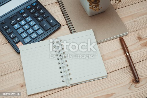 Office supplies or office work essential tools items on wooden desk in workplace, pen with notebook and calculator with copy space