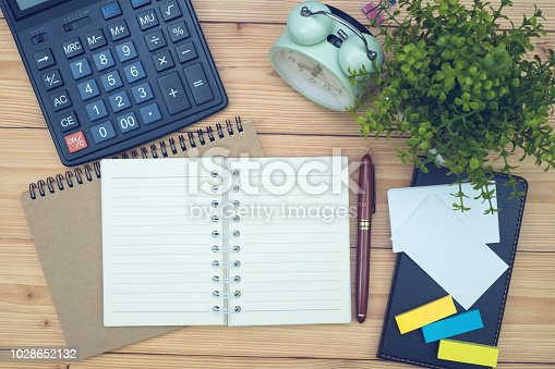 Office supplies or office work essential tools items on wooden desk in workplace, pen with notebook and calculator and alarm clock with copy space, top view